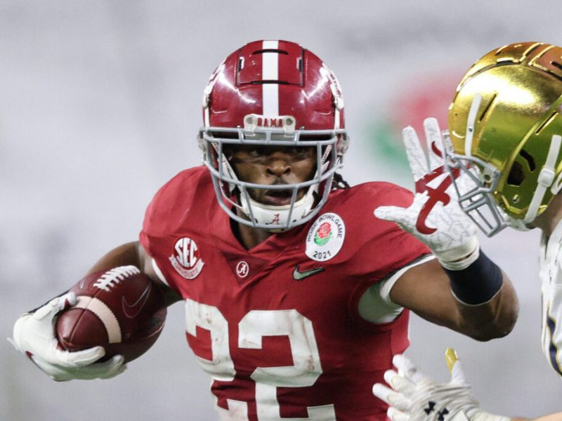 ARLINGTON, TEXAS - JANUARY 01: Running back Najee Harris #22 of the Alabama Crimson Tide stiff-arms linebacker Drew White #40 of the Notre Dame Fighting Irish during the third quarter of the 2021 College Football Playoff Semifinal Game at the Rose Bowl Game presented by Capital One at AT&T Stadium on January 01, 2021 in Arlington, Texas. (Photo by Ronald Martinez/Getty Images)