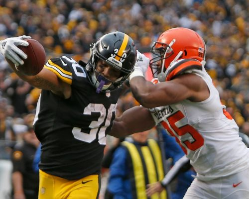 PITTSBURGH, PA - OCTOBER 28: James Conner #30 of the Pittsburgh Steelers stretches past Myles Garrett #95 of the Cleveland Browns for a 12 yard touchdown during the third quarter in the game at Heinz Field on October 28, 2018 in Pittsburgh, Pennsylvania. (Photo by Justin K. Aller/Getty Images)